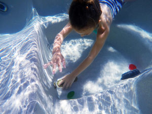 Boy diving under water for toys