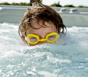 Boy in goggles half way under water