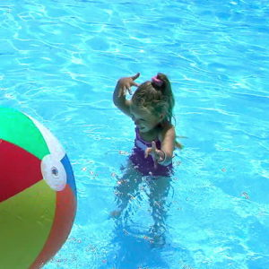 Girl in water with beach ball