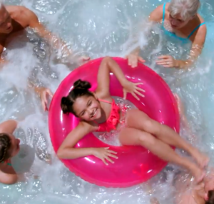 Girl in pink innertube surrounded by family
