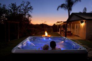 couple enjoying hot tub at sunset with firepit